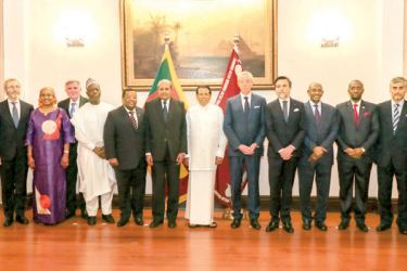 President Maithripala Sirisena with the 14 new foreign envoys at President's House in Colombo yesterday. Picture courtesy President's Media Division