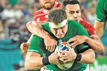 Ireland's hooker Sean Cronin (L) is tackled by Russia's scrum-half Dmitry Perov during the Japan 2019 Rugby World Cup Pool A match at the Kobe Misaki Stadium in Kobe yesterday. - AFP