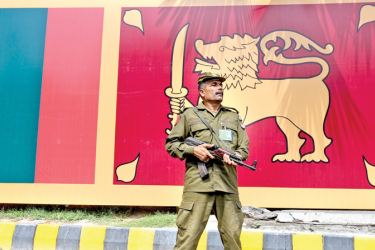 A policeman stands guard beside a Sri Lanka's flag outside the Gaddafi Cricket Stadium in Lahore on Friday. World number one Twenty20 team Pakistan take on an inexperienced Sri Lanka in the first of a three-match series in Lahore on Saturday, starting their preparation for next year's World Cup in the shortest format. - AFP