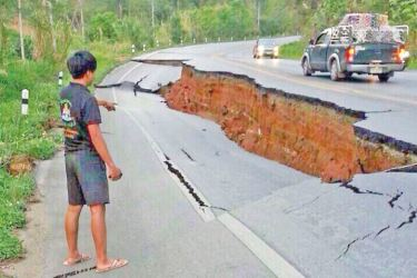 A man points a big crack on a damaged road following a strong earthquake in Indonesia.