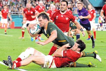 TOPSHOT - South Africa's centre Frans Steyn (C) dives to score a try past Canada's centre Ciaran Hearn (down) and  Canada's scrum-half Phil Mack (up)  during the 2019 Rugby World Cup Pool B match between South Africa and Canada at the Kobe Misaki Stadium in Kobe on Tuesday. AFP