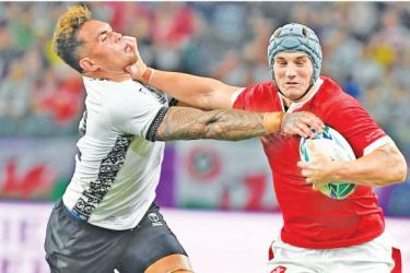 Wales' centre Jonathan Davies (R) runs with the ball past Fiji's centre Jale Vatubua during the 2019 Rugby World Cup Pool D match at the Oita Stadium in Oita on Wednesday. – AFP