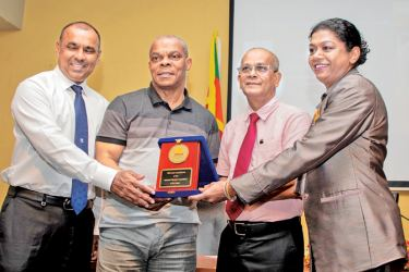National Olympic Committee officials (from left) Asanga Seneviratne, Maxwell de Silva and Susanthika Jayasinghe presenting a memento to Tonie Campbell (second left) at the Olympic House on Tuesday.