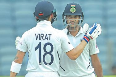 Indian batsman Mayank Agarwal (R) celebrates with captain Virat Kohli after scoring a century on the first day of the second Test match against South Africa, at Maharashtra Cricket Association Stadium in Pune yesterday. - AFP