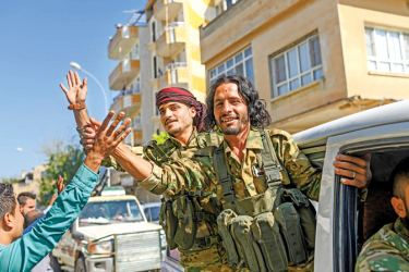 Turkish-backed Syrian opposition fighters going to Tel Abyad from the Turkish border gate towards Syria in Akcakale in Sanliurfa province on Thursday. - AFP