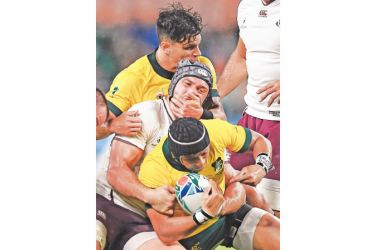 Australia's fly-half Christian Lealiifano (down) is tackled by Georgia's number 8 Beka Gorgadze (C). – AFP