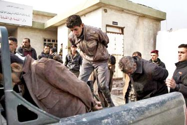 Members of the Iraqi Army load suspected Islamic State jihadis into a truck as they leave the courts before going to jail south of Mosul on December 6, 2016.