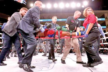 Patrick Day is being taken out from the ring after being knocked out by Charles Conwell in the super welterweight bout.