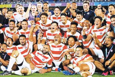 Japan's players pose for a group photo after winning the 2019 Rugby World Cup Pool A match against  Scotland at the International Stadium Yokohama in Yokohama on Sunday. – AFP