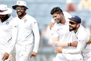 India's bowler Umesh Yadav (2R) celebrates with captain Virat Kohli (R) and Rohit Sharma (2L) after taking the wicket of South Africa's batsman Vernon Philander during the fourth day og play of second Test cricket match between India and South Africa, at the Maharashtra Cricket Association Stadium in Pune on Sunday.