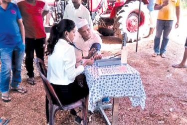 Medical professionals assessing health and fitness levels of the farmers at the medical camp alongside DIMO - Mahindra Tractor Service Camps.