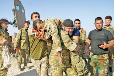 Turkish-backed Syrian fighters evacuate a wounded comrade near the border town of Ras al-Ain on October 13.