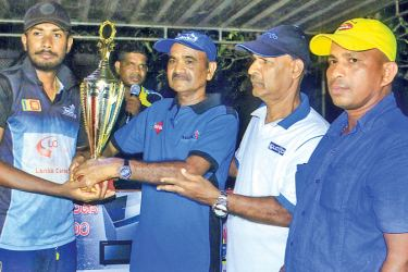 The Managing Director of R. S. Rupasinghe and company Thomas Anton presenting the championship trophy to skipper of United sports Club Indika Zoysa. The Chairman of Sarasi Promotion Kapila Bandusena and organiser of Nadee friends sports club Nihal Perera are also in the picture.