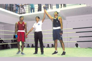 D.V.K. Thenabadu of St. Sylvester's College, Kandy being declared the winner of a preliminary bout against Trinity's Miranga Subasinghe in the Stubbs Shield Boxing Championships at the Jayathilaka Stadium in Nawalapitiya.