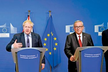 British Prime Minister Boris Johnson and President of the European Commission Jean-Claude Juncker address a European Union Summit press conference in Brussels on Thursday. - AFP