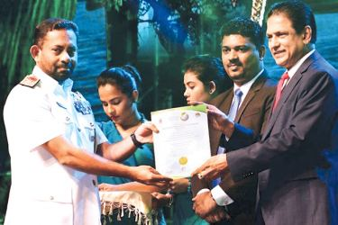 Commander Eastern Naval Area Rear Admiral Meril Wickramasinghe accepts the award at the Presidential Environmental Awards 2019 held at Nelumpokuna Theatre on Tuesday. Picture courtesy SLN
