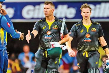 Australia's David Warner (C) and Steve Smith (R) walk off the field after victory during the Twenty20 match against Sri Lankia at the Gabba in Brisbane on Wednesday. – AFP