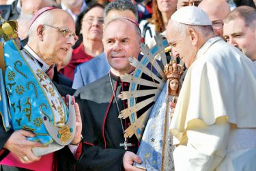 The image of Argentina's saint patron, the Our Lady of Lujan (R) and a replica are exchanged between British and Argentinian officials during Pope Francis weekly general audience on the Saint Peters' square on Wednesday at the Vatican. -AFP