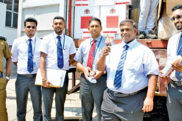 Customs officials with the stock of foreign cigarettes which they had seized, at the Ceylon Tobacco Company destruction yard yesterday. Picture by Sarath Peiris