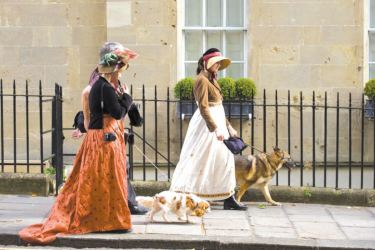 Two women in Regency costume walking dogs  through Bath during the city's annual Jane Austen festival