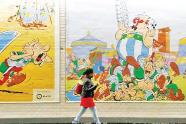 A woman walks next to a draw especially designed to commemorate the 60th anniversary of France's famous comic characters Asterix and Obelix on October 9, 2019 at the Rome metro station in Paris.