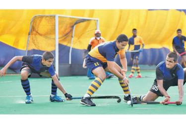 Royal skipper Sachithra Malshan (centre) is up against the Thomian defenders R.H. Rambukpotha (left) and C.H. Hewawasam during their 20th annual hockey encounter at the Astro Turf in Reid Avenue yesterday. (Picture by Samantha Weerasiri)
