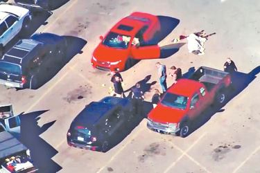 Police are seen looking at a red vehicle (pictured, with the door open, left) that appears to have multiple bullet holes in the windshield. A body is seen lying next to the car, outside a Walmart store in Duncan, Oklahoma.