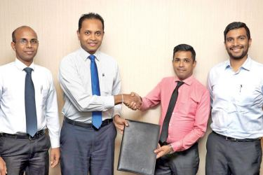 Commercial Bank's Head of Card Centre Thusitha Suraweera and Fashion Bug Area Manager Mohamed Faishad exchange the agreement in the presence of Fashion Bug CEO Aqeill Ahamed Subian and Junior Executive Officer of the Bank's Card Centre Wishan Fernando.