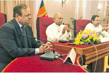 Foreign Relations Minister Dinesh Gunawardena speaks to the media in Colombo on Wednesday on the Swiss Embassy issue. State Foreign Relations Minister Susil Premajayantha and Foreign Relations Ministry Secretary Ravinatha Aryasinha are also in the picture.