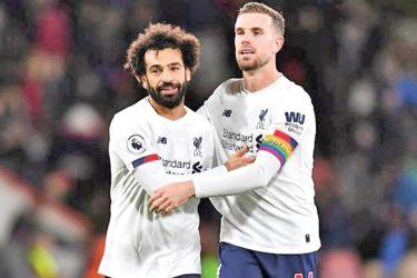 Liverpool's Mohamed Salah and Jordan Henderson celebrate after the match.