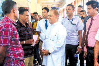 INSPECTION TOUR: Passenger Transport, Power and Energy Minister Mahinda Amaraweera who made an inspection tour of the RMV Head Office in Narahenpita yesterday seen talking to employees.