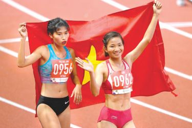 Oahn Thi Nguyen (R) from Vietnam celebrates with compatriot Phuon Anh Khuat (L) after winning in the women's 1500 of the athletics event at the SEA Games (Southeast Asian Games) in the athletics stadium in Clark City, Capas, Tarlac province north of Manila on December 8, 2019. (AFP)