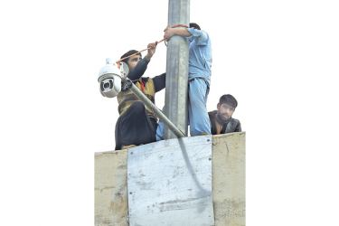 Pakistani technicians install a security camera outside the Pindi Cricket Stadium in Rawalpindi on Tuesday, ahead of the first Test cricket match between Pakistan and Sri Lanka. – AFP