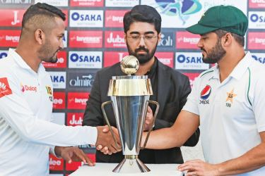 Pakistan's captain Azhar Ali (R) and his Sri Lankan counterpart Dimuth Karunaratne (L) shakes hands in front of the Test series trophy at the Pindi Cricket Stadium ahead of the first Test cricket match between Pakistan and Sri Lanka in Rawalpindi on Tuesday. – AFP