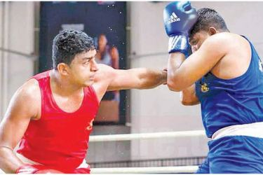 Rumesh Sandakelum (red) lands a left on his Nepal opponent on his way to  win the gold medal in the 81kg boxing final at the SAG.