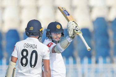 Sri Lanka's Dimuth Karunaratne (R) celebrating with teammate Oshada Fernando after scoring his half-century during the first day of the first Test cricket match against Pakistan at the Pindi Cricket Stadium on Wednesday. AFP