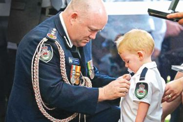 The Fire Service Commissioner pins a posthumous commendation for bravery and service on volunteer firefighter Geoffrey Keaton's son Harvey Keaton.