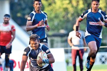 Police Sports Club winger Sachith Silva is about to score a try with support coming from two team mates in their Dialog 'A' Division League Rugby Match against CH and FC played at Police Park yesterday which Police won 36-22. Picture by Samantha Weerasiri