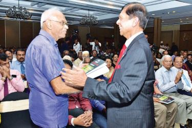 Senior Economic Adviser to the Prime Minister, Ajith Nivard Cabraal presenting a copy of 'The great bond scam cover-up' to former Deputy Governor of the Central Bank Dr. W.A. Wijewardena at Ramada on Friday.