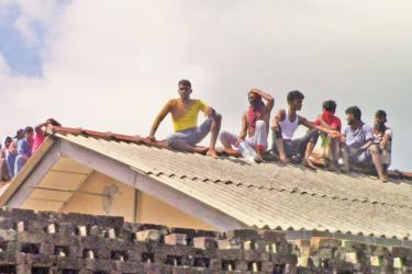Prisoners protest on the roof on the Batticaloa Prison yesterday after a prisoner's death. Picture by Batticaloa Special Corr.