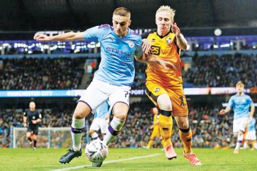 Manchester City's Taylor Harwood-Bellis in action with Port Vale's Mark Cullen in an FA Cuo third round match.