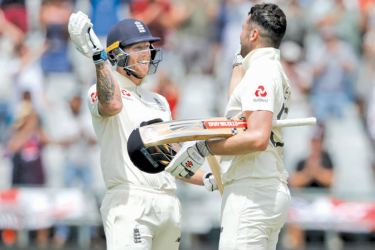England's Dom Sibley (R) celebrates with England's Ben Stokes (L) after scoring a century (100 runs) during the fourth day of the second Test cricket match between South Africa and England at the Newlands stadium in Cape Town on January 6. AFP