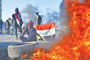 Iraqi demonstrators block a road with burning tyres in the central shrine city of Najaf on Sunday to protest turning the country into an arena for US-Iran conflicts. Iraq's Parliament voted on Sunday calling on US troops stationed in Iraq to leave the country.- AFP