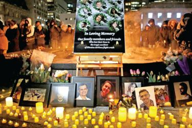 An altar with photographs of the victims who were killed in a plane crash in Iran is seen as people gather around to held a vigil in their memories on Thursday in Ottawa, Canada. - AFP