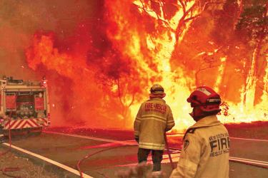 Fire and Rescue personal run to move their truck as a bushfire burns next to a major road and homes on the outskirts of the town of Bilpin, in Sydney, Australia.