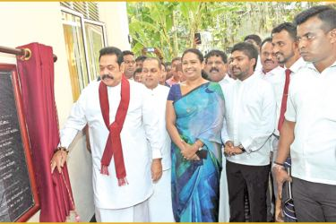 Prime Minister Mahinda Rajapaksa revealing the paediatric ward complex plaque, while Health Minister Pavithra Vanniarachchi and others look on.