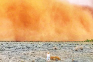 A child running towards a dust storm in Mullengudgery in New South Wales. - Dust storms hit many parts of Australia's western New South Wales as a prolonged drought continues. - AFP