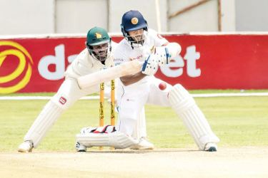 Sri Lanka's Kusal Mendis (R) prepares to play a shot as Zimbabwe's Regis Chakabva (L) looks on during the third day of the first Test cricket match at the Harare Sports Club in Harare on Tuesday. - AFP