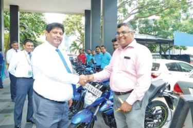 SLIC Chairman Jagath Wellawatta presents the new motor bicycles to a Motor Technical Officer