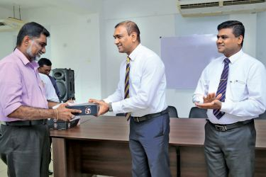Head of domestic cricket operations SLC Chinthaka Edirimanne handing cricket balls to the master in charge of a school.